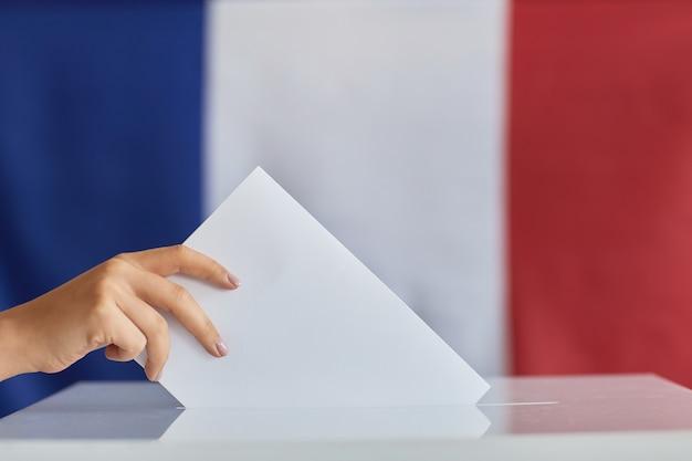 Primer plano de mujer poniendo el sobre en la caja durante la votación