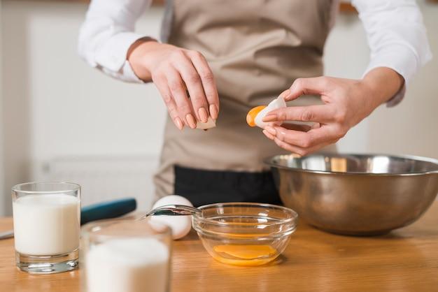 Primer plano de una mujer poniendo yema de huevo en el recipiente de vidrio