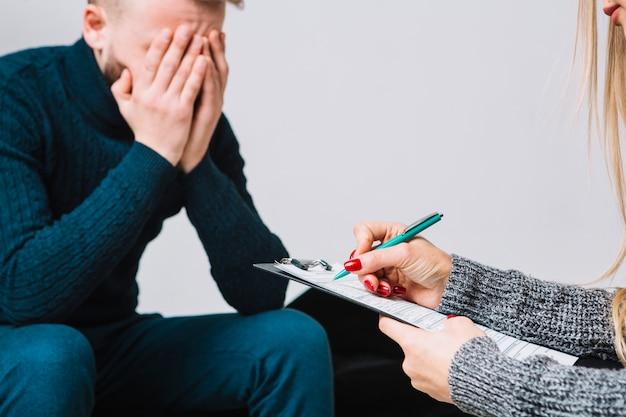 Primer plano de mujer psicóloga con cliente deprimido masculino tomando notas