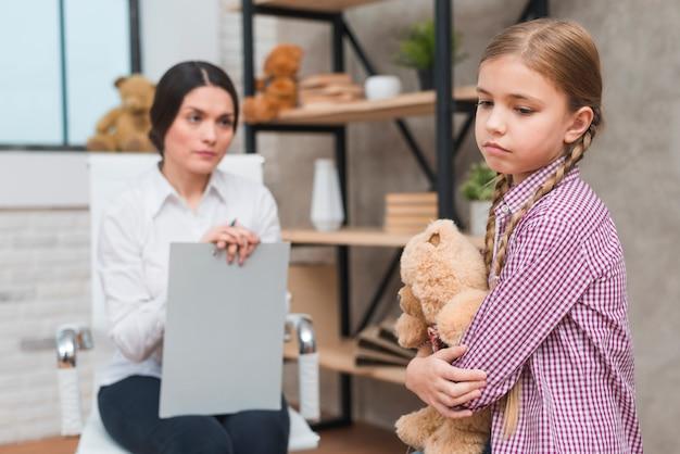 Primer plano de mujer psicóloga mirando a una niña triste sosteniendo un oso de peluche