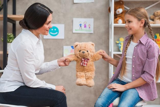 Primer plano de mujer psicóloga y niña sonriente sosteniendo peluche en manos
