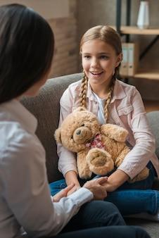 Primer plano de mujer psicóloga tomados de la mano de su paciente con osito de peluche