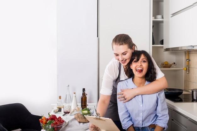 Primer plano de una mujer que ama a su amigo mirando receta en el portapapeles en la cocina