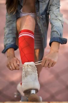 Primer plano de una mujer que ata el cordón de patinador