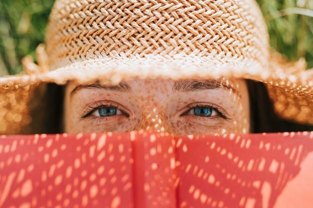 Primer plano de mujer que cubre su rostro con un libro rojo