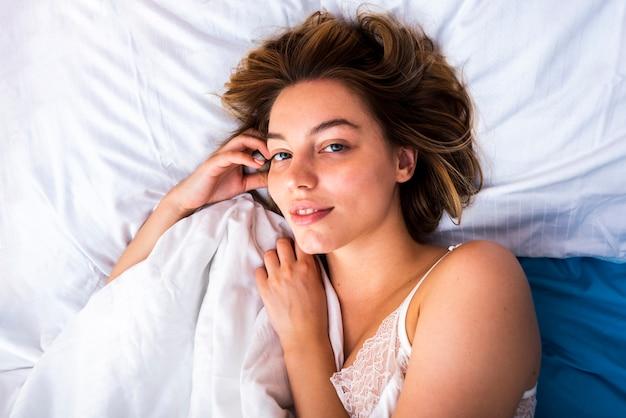 Primer plano de una mujer que despierta mirando a la cámara