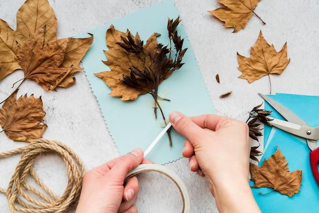 Primer plano de una mujer que pega las hojas de otoño con cinta blanca sobre fondo texturizado