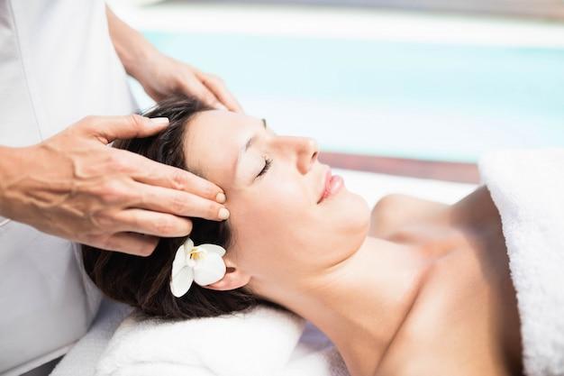 Primer plano de mujer que recibe un masaje de cabeza de masajista en un spa