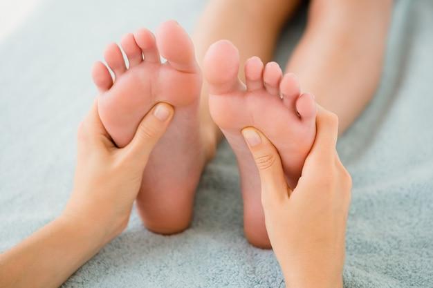 Primer plano de una mujer que recibe masaje en los pies
