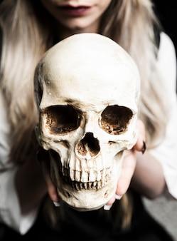 Primer plano, de, mujer que sostiene el cráneo