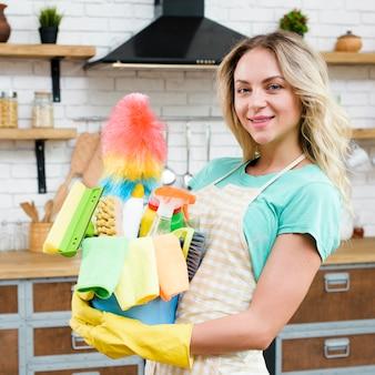 Primer plano de una mujer que sostiene el cubo de herramientas y productos de limpieza