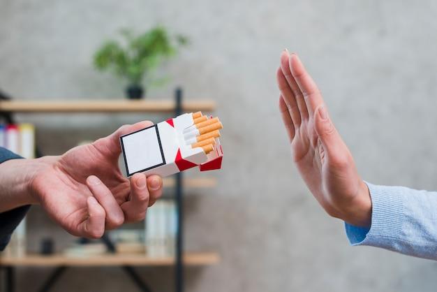 Primer plano de una mujer rechazando los cigarrillos ofrecidos por su colega