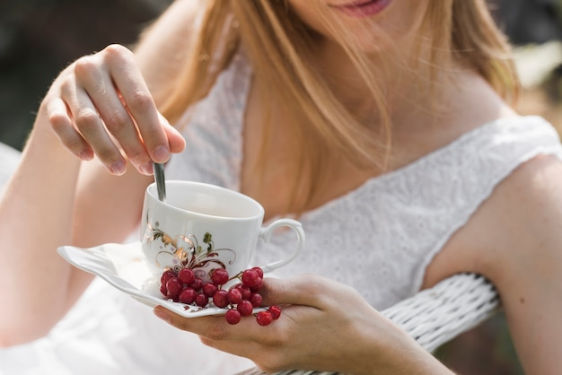Primer plano de mujer revolviendo el café con una cuchara en la taza de cerámica