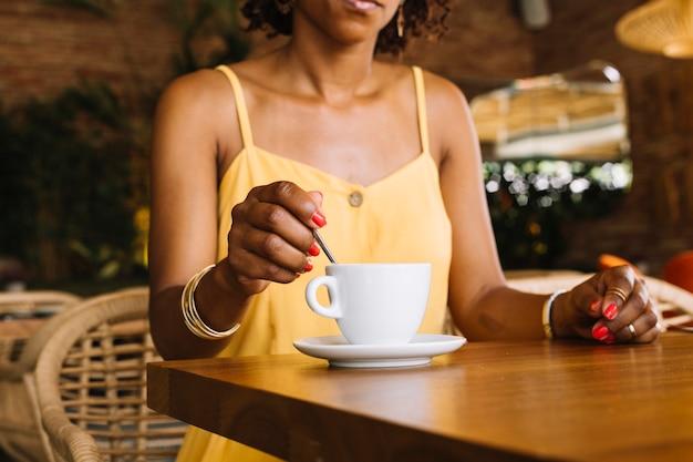 Primer plano de una mujer revolviendo la cuchara en la taza de café con leche en la mesa