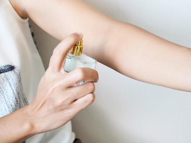 Primer plano de mujer rociando perfume en los brazos agregue fragancia al cuerpo.