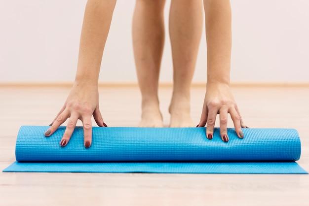 Primer plano mujer rodando estera de fitness después del ejercicio