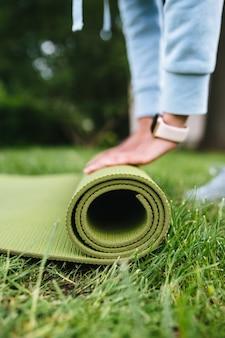 Primer plano de mujer rodillo plegable fitness o esterilla de yoga después de hacer ejercicio en el parque