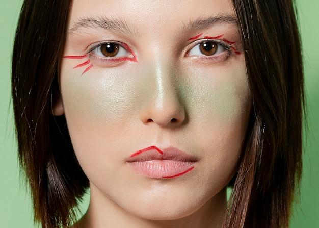 Primer plano de mujer con rostro artístico pintado