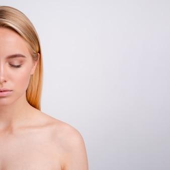 Primer plano mujer rubia con los ojos cerrados y espacio de copia
