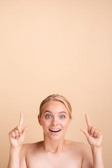 Primer plano mujer rubia sonriente apuntando hacia arriba