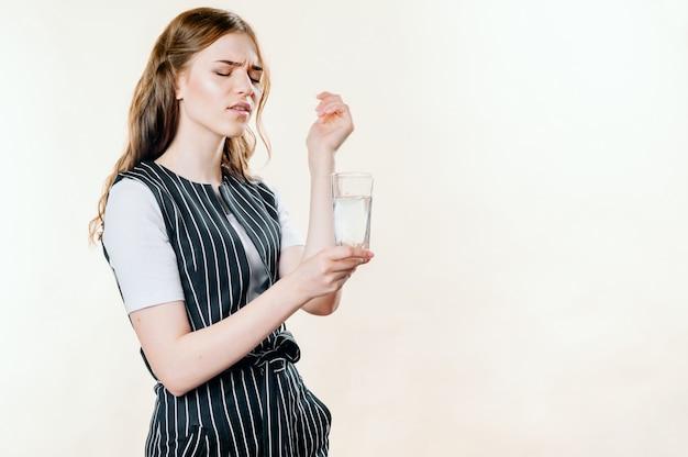 Primer plano de una mujer rubia con un terrible dolor de cabeza con una tableta y un vaso de agua