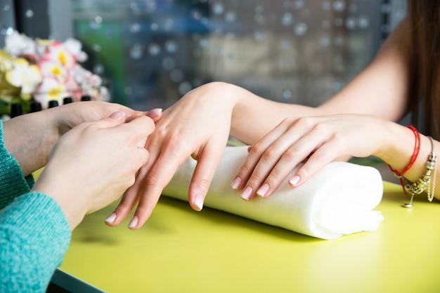 Primer plano de una mujer en un salón de uñas recibiendo una manicura