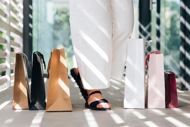 Primer plano de mujer en sandalias cerca de bolsas de compras