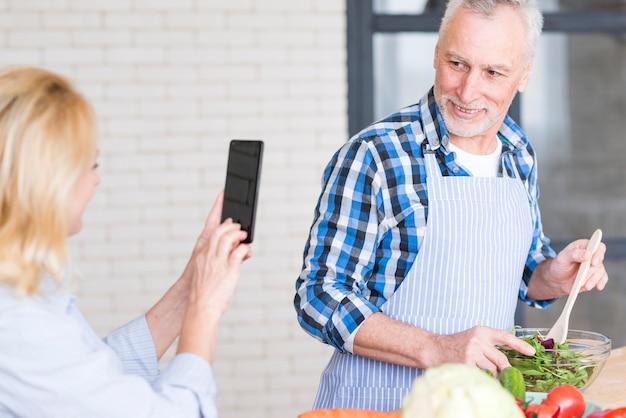 Primer plano de una mujer senior tomando una foto de su esposo preparando la ensalada en el tazón en el teléfono móvil