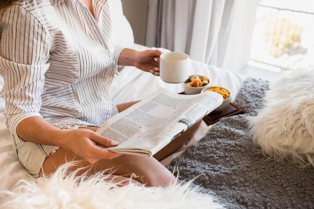 Primer plano de una mujer sentada en la cama con periódico y taza de café en la mano