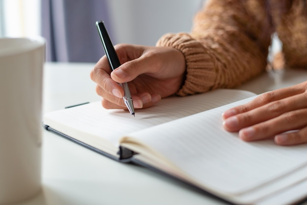 Primer plano de mujer sentada a la mesa y horario de planificación