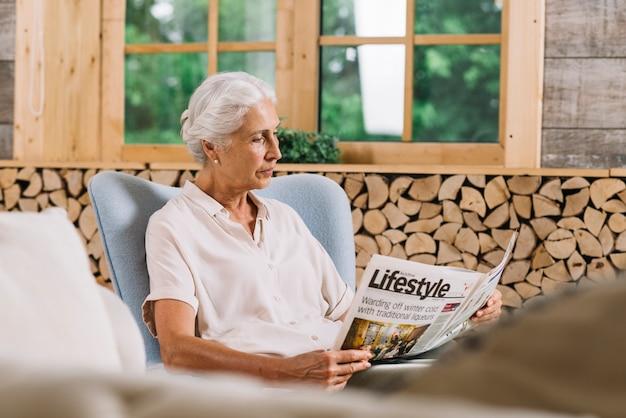 Primer plano de mujer sentada en la silla leyendo el periódico