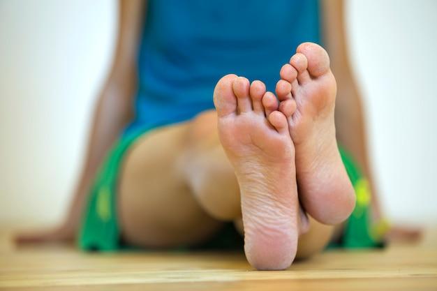 Primer plano de mujer sentada en el suelo con los pies descalzos. concepto de cuidado de las piernas y tratamiento de la piel.