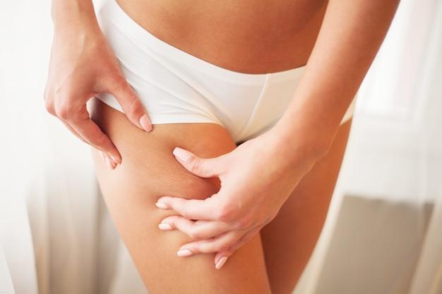 Primer plano de mujer sexy caliente con la mano pellizcando la piel