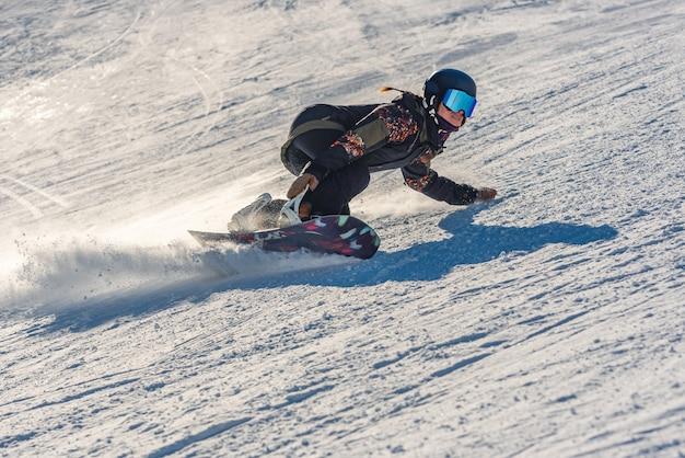 Primer plano de una mujer snowboarder en movimiento sobre una tabla de snowboard en una montaña