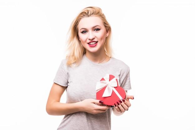 Primer plano de mujer sonriente con caja de regalo en forma de corazón rojo