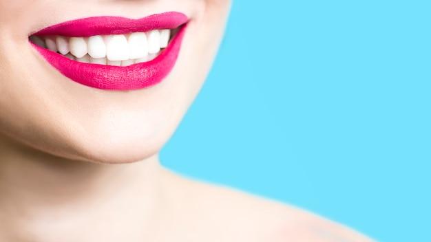 Primer plano de una mujer sonriente con dientes blancos sanos, lápiz labial rojo, piel limpia.