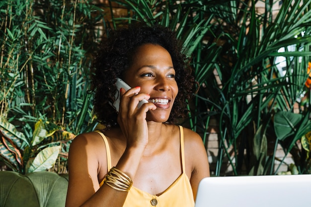 Primer plano de mujer sonriente joven hablando por teléfono móvil