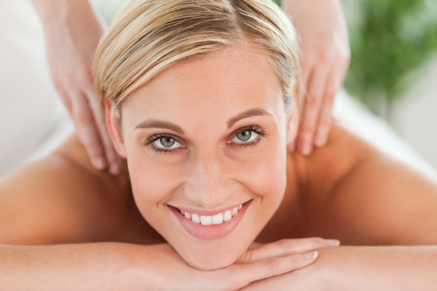 Primer plano de una mujer sonriente que se relaja en una tumbona durante un masaje mira a la cámara