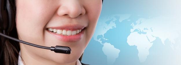 Primer plano de mujer sonriente trabajando en un centro de llamadas