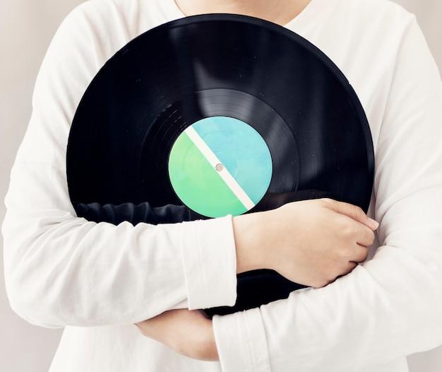 Primer plano de mujer sosteniendo disco de disco de vinilo de música