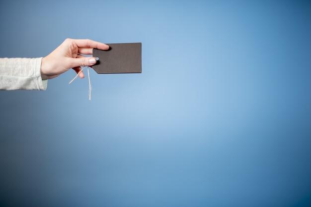 Primer plano de una mujer sosteniendo una etiqueta en blanco con un fondo azul, ideal para escribir texto