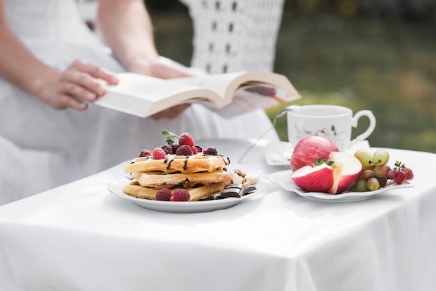 Primer plano de una mujer sosteniendo un libro en la mano sentado detrás de la mesa de desayuno al aire libre