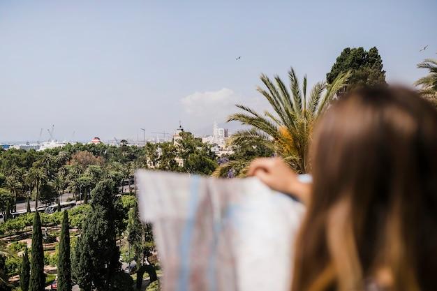 Primer plano de mujer sosteniendo el mapa frente a telón de fondo de la ciudad