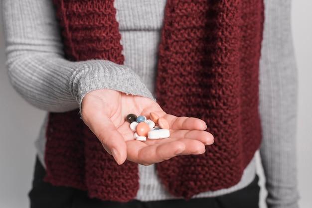 Primer plano de mujer sosteniendo muchas pastillas en la mano