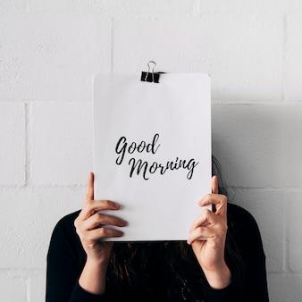Primer plano de una mujer sosteniendo papel adjuntar con clip y texto de buena mañana delante de su cara