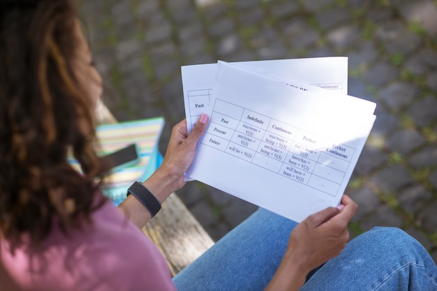 Un primer plano de una mujer sosteniendo papeles en las manos