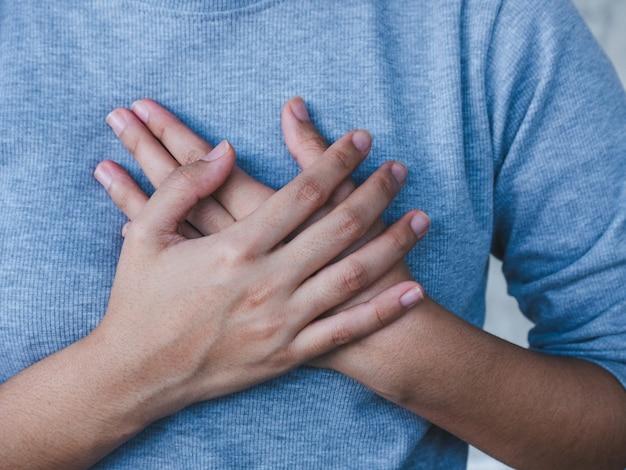 Primer plano de mujer sosteniendo el pecho, mujer que tiene un ataque al corazón