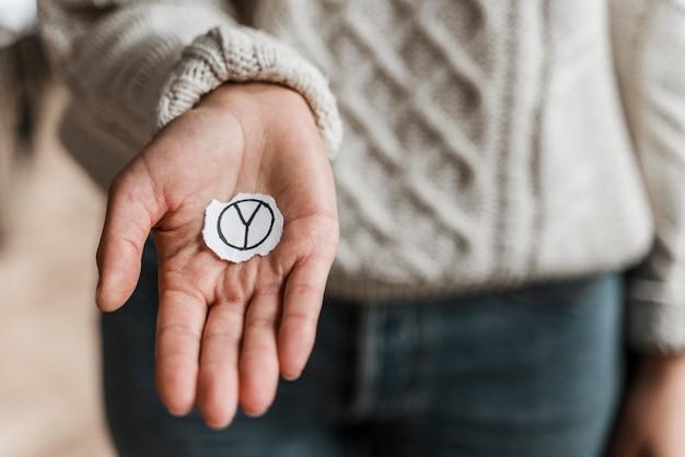 Primer plano de una mujer sosteniendo el símbolo de la paz