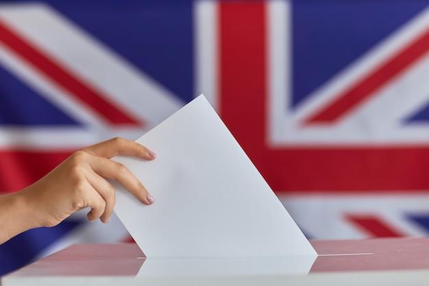 Primer plano de mujer sosteniendo un sobre mientras vota en la cabina de votación