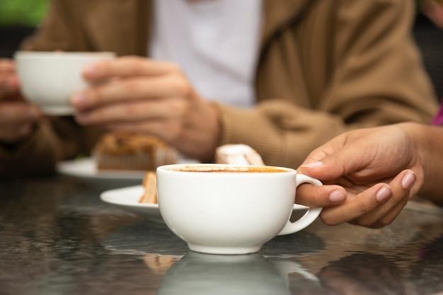 Primer plano de mujer sosteniendo la taza de café